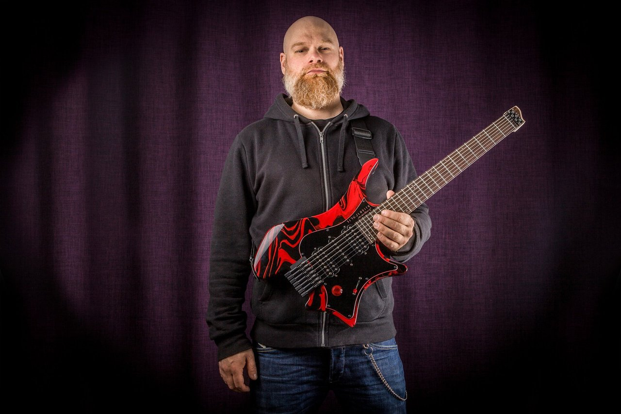 Per Nilsson holding Headless Guitar Boden Singularity 7-string Red Swirl