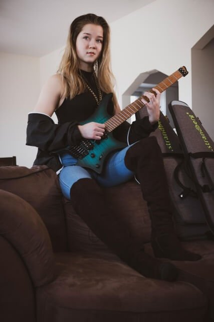 Erin Coburn on sofa with headless NT strandberg guitar