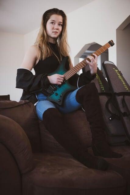 Erin coburn on sofa with Strandberg headless NT teal guitar