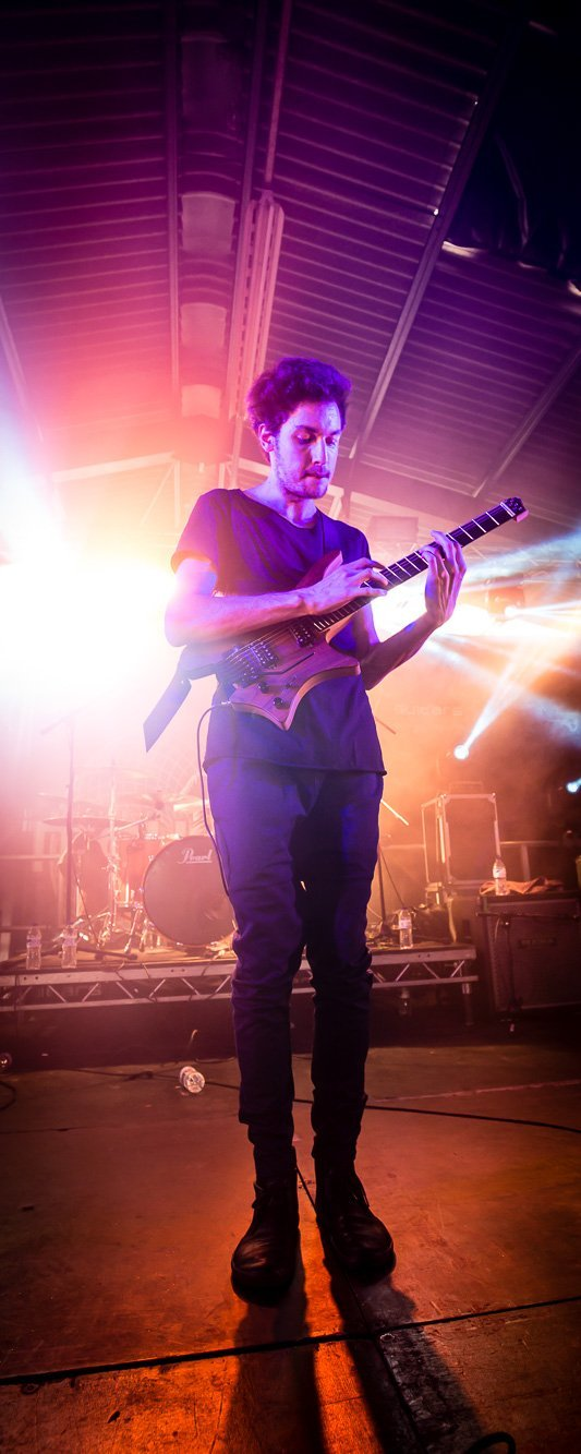 Plini on stage with his signature guitar