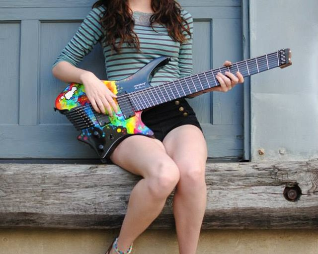 sara longfield sitting with signature guitar
