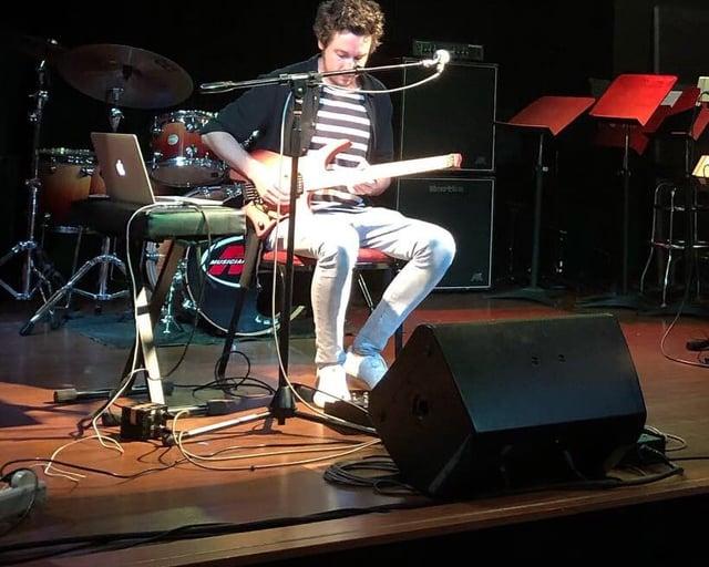 Plini on stage with his signature strandberg headless guitar