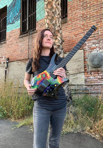 Sara Longfield posing with her signature headless guitar