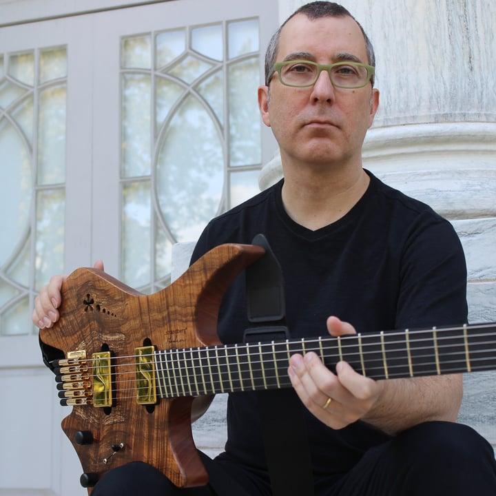Gustavo Assis Brasil holding a headless strandberg guitar