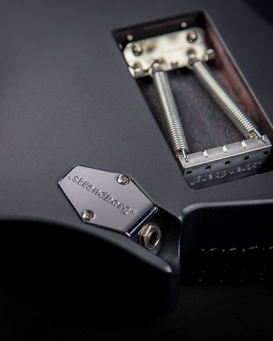 Headless Boden Graphite Classic 7 featuring a black pearloid pickguard and roasted maple fretboard closeup