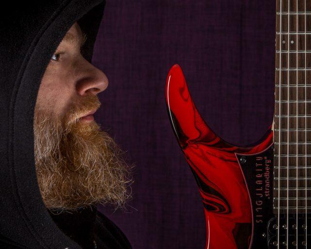Per Nilsson holding Headless Guitar Boden Singularity 7-string Red Swirl