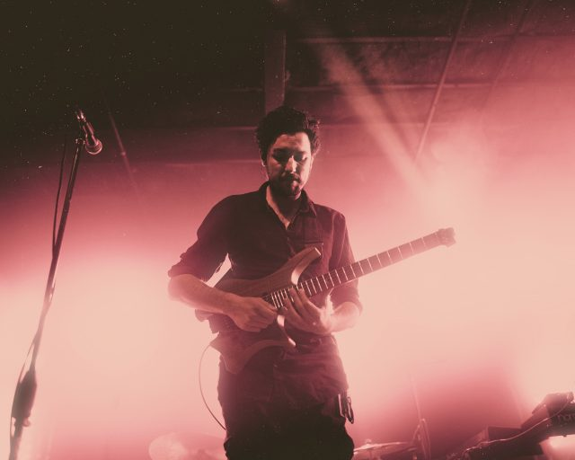 Plini on stage with his signature headless guitar