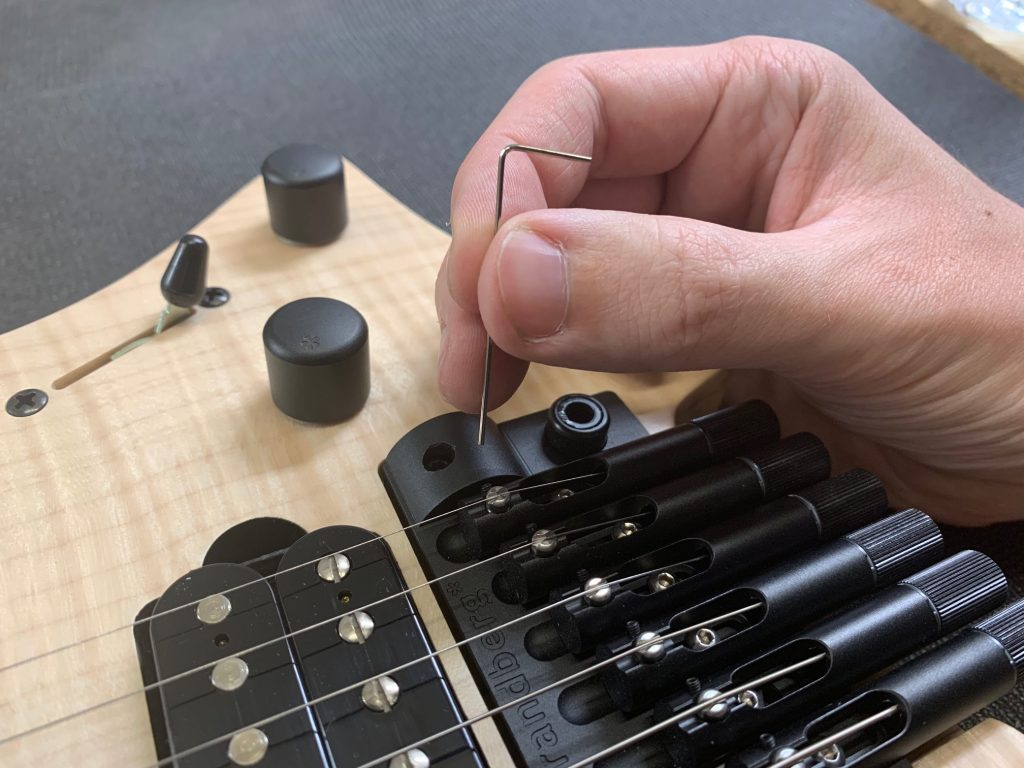 Headless guitar bridge tuning closeup
